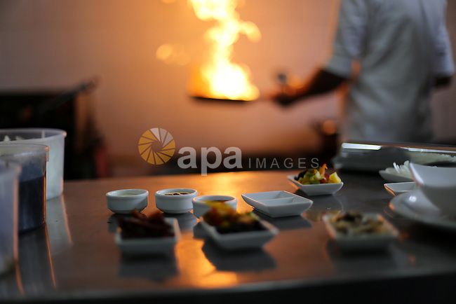 A Palestinian chef cooks Chinese food at restaurant in Gaza city on Dec. 13, 2015. Photo by Mohammed Asad