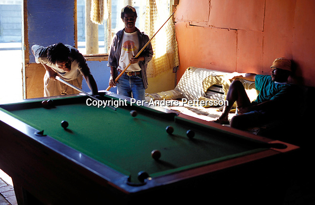 disiune00008.Social Issues. Esitin Josef (middle), age 32 and Tomas Ngcawe (right) and an unidentified friend, all unemployed, men playing pool early in the morning at Dan's cool spot, an illegal bar (shebeen) on August 10, 2001 in Site C Khayelitsha, a township about 35 kilometers outside Cape Town, South Africa. Khayelitsha is one of the poorest and fastest growing townships in South Africa. People usually come from the rural areas in Eastern Cape province to find work as maids and laborers. Most people don't find work and the unemployment rate is very high, together with lot of violence and a growing HIV-Aids epidemic itÕs a harsh area to live in..©Per-Anders Pettersson/ iAfrika Photos.