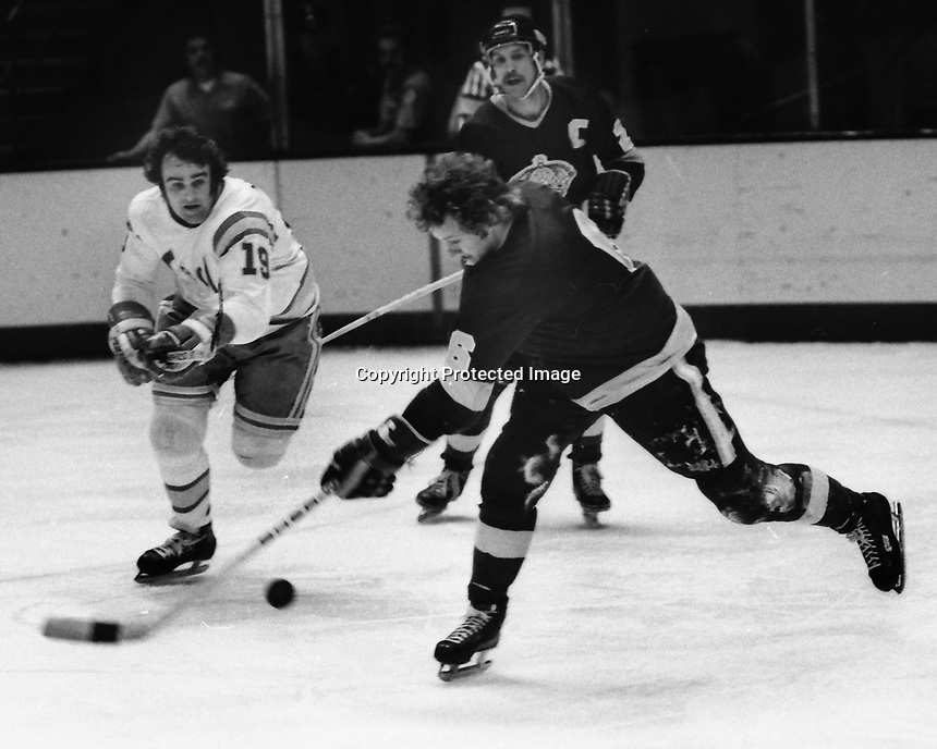 Seals vs LA Kings 1975. Kings Sheldon Kannegiesser shoots past Seals Jim Moxey. (photo/Ron Riesterer)