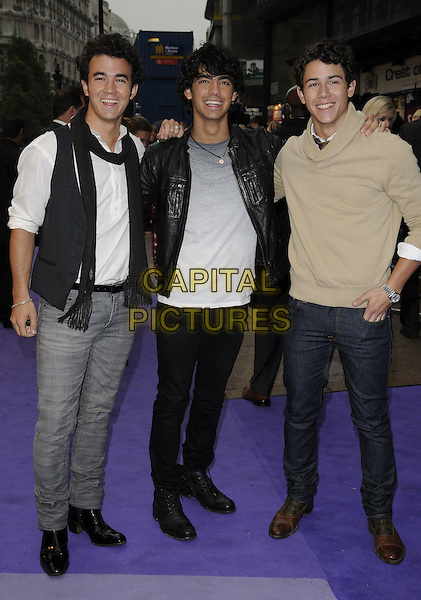 """JONAS BROTHERS - KEVIN JONAS, JOE JONAS & NICK JONAS .The UK Film Premiere of """"Jonas Brothers 3D Concert Experience"""" at the Empire cinema, Leicester Square, London, England..May 13th 2009.full length black leather jacket scarf white top beige jumper brown tie jeans denim grey gray t-shirt waistcoat .CAP/CAN.©Can Nguyen/Capital Pictures."""