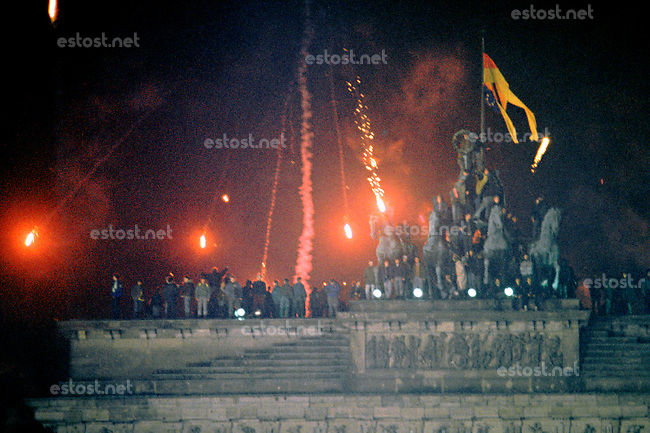 DEUTSCHLAND, 31.12.1989.Erstes gesamtdeutsches Neujahrsfest nach dem Fall der Mauer: Freiheitstrunkene Kletterer auf dem Brandenburger Tor..First unified new year's eve after the fall of the wall: Liberty-drunk climbers on the Brandenburg Gate..© Martin Fejer/EST&OST