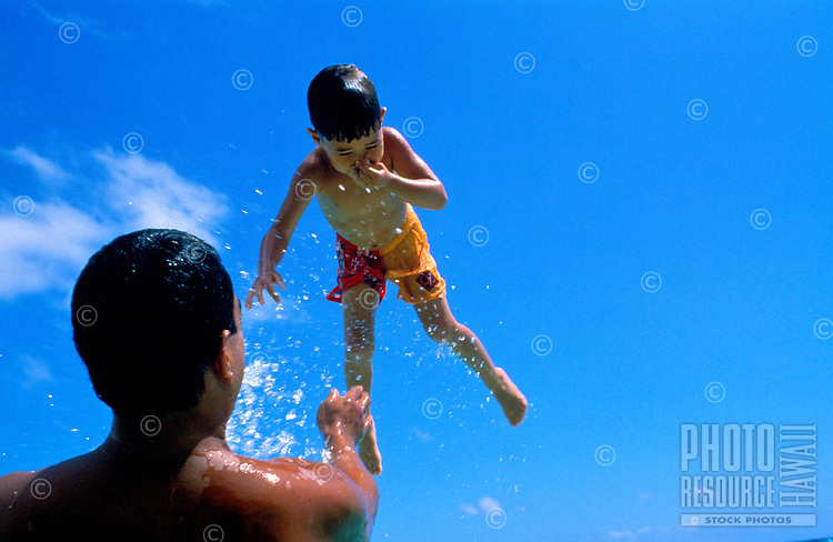 A young boy is tossed in the air by his father at a beach on Oahu,