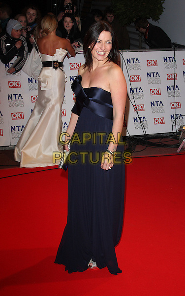 DAVINA McCALL.The 15th National Television Awards held at the O2 Arena, London, England. .January 20th, 2010 .NTA NTAs full length black navy blue strapless dress side.CAP/ROS.©Steve Ross/Capital Pictures.