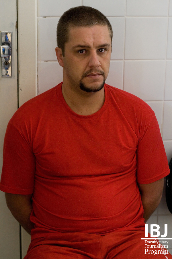 A prisoner, handcuffed, sits by an office at Floramar Prison in Divinopolis, Brazil. IBJ Fellow Dr. Saliba is hoping to reach out to prison communities across Brazil to inform them of their right to habeas corpus.