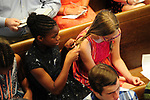 Bella Pratt keeps and eye on the new Transitional Pastor Carolyn Poteet while she braids the hair of Leah Bonnet during the contemporary service Sunday, June 25, 2017 at Mt. Lebanon Evangelical Presbyterian Church in Mt. Lebanon. Bella's father plays bass guitar  with the worship team musicians. (Jim Mendenhall/Post-Gazette)