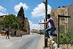 A Palestinian youth leaps from a wall into the street after spotting approaching IDF soldiers during brief clashes following a nonviolent demonstration against Israel's controversial separation barrier in the West Bank town of Beit Jala near Bethlehem on 27/06/2010.