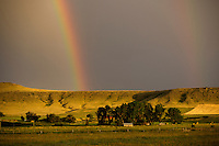 Rainbows touch farmland outside Simms, Montana, USA.
