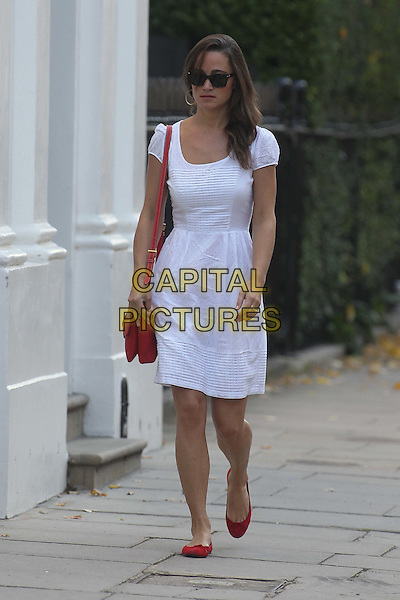 Pippa Middleton arrives for work, London, England..29th September 2011.full length white dress red bag shoes  sunglasses shades  .CAP/HIL.©John Hillcoat/Capital Pictures.