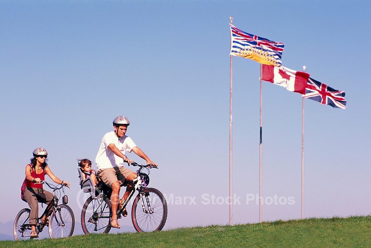 Stanley Park, Vancouver, BC, British Columbia, Canada - Family cycling on Bikes on Seawall in Summer - BC, Canadian, and Union Jack Flags