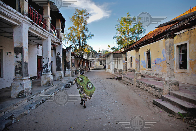 A woman walks down a street past deserted and ruined buildings in the town of Ibo on Ibo Island.
