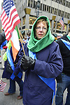 March 16, 2013 - New York, NY, U.S. - Woman holding American flag and Irish flag,, as she gets ready to march with Quinnipiac College group in  the 252nd annual NYC St. Patrick's Day Parade.