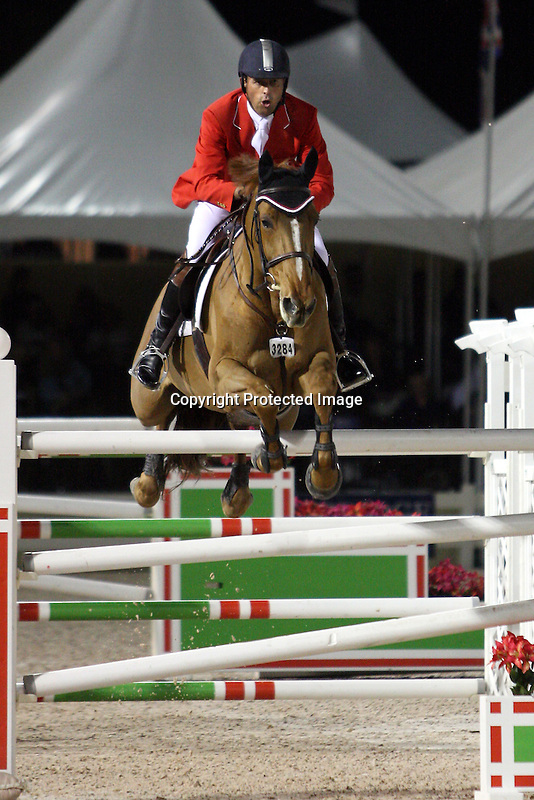 Yann Candele and Mustique compete for Canada in the final round of the $75,000 FEI Nations Cup, an Olympics-style show jumping event, on Friday night, Feb. 28, 2009, during the Winter Equestrian festival in Wellington, Fla. Canada won the eight-nation, two-round competition before the first sellout (8,000) at the recently-renovated Palm Beach International Equestrian Center. Canada edged Ireland and Great Britain (tie) for the blue ribbons, followed by the United States. Also competing were teams from Argentina, France, Mexico and Venezuela. Thousands of cheering, flag-waving fans packed the International Arena at the WEF grounds for the Nations Cup, reportedly the oldest and most prestigious team show jumping competition in the world. Photo by Bob Markey II