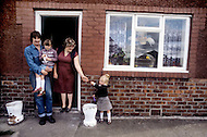 August 1981. Newcastle area, England. Michael and Joan Dempsey posing with their children in front of their house in Consett. Michael has been unemployed from the construction business for 2 years, and Joan works as a shop assistant.