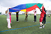 Group of children playing the parachute game on a playing field at their local leisure centre,