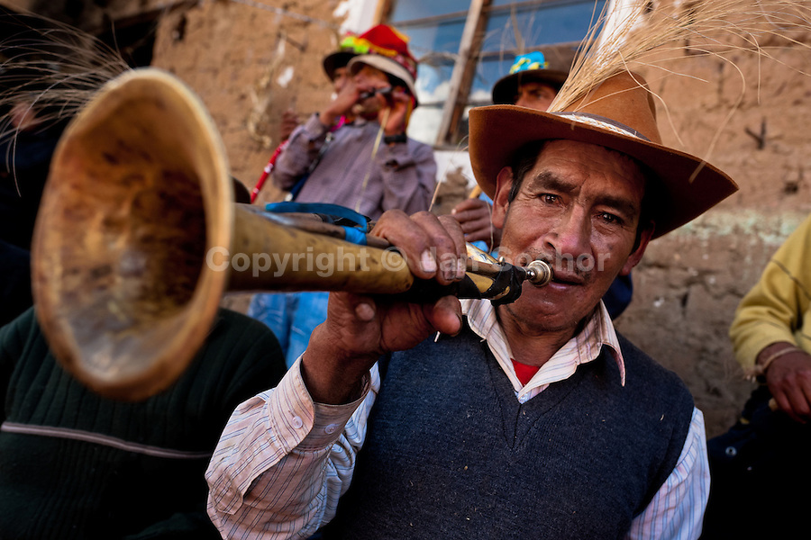 A Peruvian peasant plays a trumpet during the Yawar Fiesta, a ritual fight between the condor and the bull, held in the mountains of Apurímac, Cotabambas, Peru, 30 July 2012. The Yawar Fiesta (Feast of Blood), an indigenous tradition which dates back to the time of the conquest, consists basically of an extraordinary bullfight in which three protagonists take part - a wild condor, a wild bull and brave young men of the neighboring communities. The captured condor, a sacred bird venerated by the Indians, is tied in the back of the bull which is carefully selected for its strength and pugnacity. A condor symbolizes the native inhabitants of the Andes, while a bull symbolically represents the Spanish invaders. Young boys, chasing the fighting animals, wish to show their courage in front of the community. However, the Indians usually do not allow the animals to fight for a long time because death or harm of the condor is interpreted as a sign of misfortune to the community.