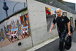 Nov 10, 2009 - Tokyo, Japan - A foreign man walks past large pictures depicting the collapse of the Berlin Wall along the wall of the German Embassy in Tokyo.