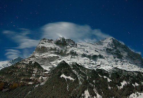 A winter landscape on a clear night with stars in the sky, of snow blowing from the Alps in Grindelwald, Switzerland.