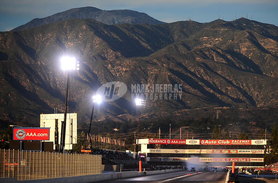Nov 13, 2010; Pomona, CA, USA; NHRA funny car drivers John Force (left) and Matt Hagan do their burnouts during qualifying for the Auto Club Finals at Auto Club Raceway at Pomona. Mandatory Credit: Mark J. Rebilas-