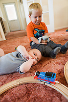 A toddler and his baby brother watch a blue toy train locomotive go around a wooden track on the living room carpet...Taken 09/07/11.Hampshire, England, UK