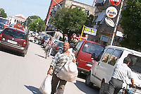 Street scene with cars, bicycles, pedestrians, a man walking with two big sacks with goods to sell. Shkodra. Albania, Balkan, Europe.