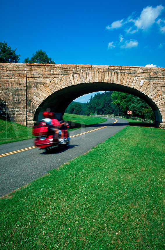 Red motorcycle approaching stone bridge