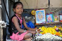 INDIA, girl works in flower shop / INDIEN, junges Maedchen faedelt Jasmin Blueten auf und verkauft Blumen