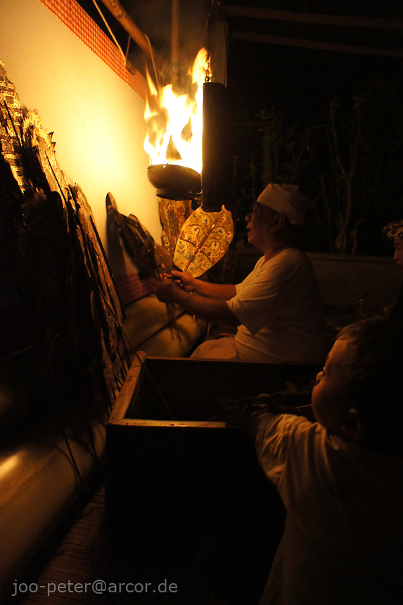 balinese wayang kulit in action - Singaraja, Bali, archipelago Indonesia, 2010. villagers getter to see the performance. An oprchestra is playing and the dayang (puppet player) plays all characters. Wayang Kulit is not only popular entertainment often comical aspects, like in this evening performance, it also has religious dimension with priest-like function of the dayang, who gives blessings here after performance.