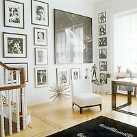 An entire wall of the living room has been hung with framed black-and-white photographs and the slipper chair next to the metal floor sculpture is a Christian Liagre design