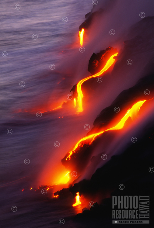 At dusk, glowing lava flows into the Pacific Ocean and creates steam, Hawai'i Volcanoes National Park, Big Island.