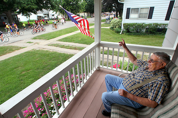 "Bud Allan, 81, takes in the parade of RAGBRAI riders flowing down Main Street in Baxter on July 28 along RAGBRAI XXXIX.  ""I just can't hardly believe it,"" he said of the crush of riders hitting town."