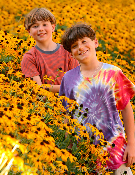 ow young boys sanding in a field of black eye susans.