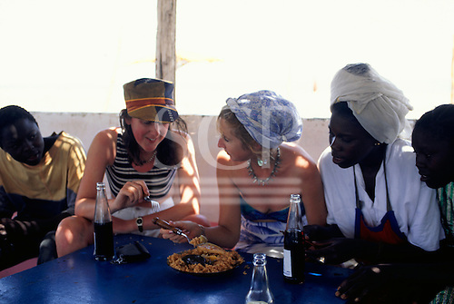 Banjul, Gambia. Tourists trying local food in a small bar restaurant while local people look on.