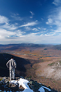 A hiker takes in the view from the summit of Mount Flume in Lincoln, New Hampshire USA.