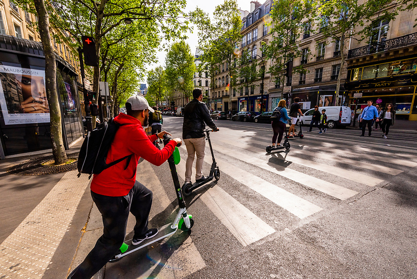 Electric scooters are trendy now in Paris. These riders are crossing Place de l'Opera to Boulevard des Capucines, Paris, France.