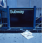 New York City Subway entrance with newspapers laying on sidewalk