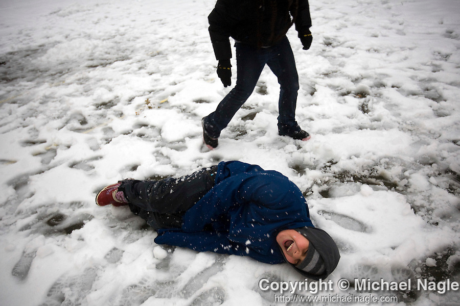BROOKLYN - DECEMBER 19, 2008:  Logan Donato, 10, is attacked by snowballs thrown by his cousin Ariana Pagan, 8, in a playground next to the Marcy Projects during a snow storm on December 19, 2008 in Brooklyn.    (Photo by Michael Nagle)