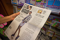 A women reads a copy of Women's Wear Daily (WWD) at a newsstand in New York on Wednesday, August 20, 2014. Penske Media Corp. has purchased Fairchild Fashion Media from Conde Nast for an undisclosed sum. Titles include WWD, Footwear News and Beauty Inc. and include a conference and event unit. Conde Nast purchased Fairchild from Disney 15 years ago. (© Richard B. Levine)