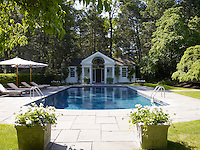 The outdoor swimming pool is sheltered by mature hedges and shaded by the trees in the garden