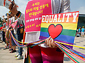 Participants hold signs during a gay pride parade in Seoul