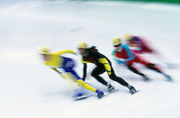 skaters on a short track racing in a blur