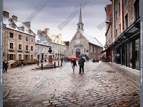 Rainy day view of Notre Dame des Victoires Roman Catholic Church and statue of Louis XIV in Place Royale. Royal Square with boutiques, restaurants and people on the terrace of Maison Smith cafe. Old Quebec City. Quebec, Canada. Église Notre-Dame-des-Victoires, Ville de Québec.