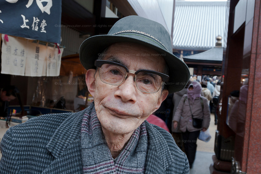 An older Japanese man at  Toganji Temple in Sugamo, Tokyo, Japan. Saturday, January 24th 2009. Sugamo is affectionately known as the old lady Harajuku, in reference to the Mecca for youth fashions in the South of Tokyo, and is a popular place for Tokyo's increasingly aged population.