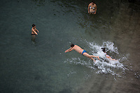 Locals swim on a public beach on Saturday, Sept. 19, 2015, in Sorrento, Italy. (Photo by James Brosher)