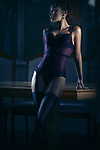 Sensual glamour portrait of a sexy beautiful woman wearing a purple corset and stockings standing leaning against a table in dim night light Image © MaximImages, License at https://www.maximimages.com