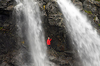 Hikers at waterfalls below Cataract Glacier, Harriman Fiord, Prince William Sound, Chugach National Forest, Alaska.