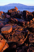 A pile of red volcanic boulders on Kahoolawe with the island of Maui in the distance.
