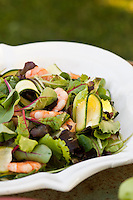 Detail of a bowl of salad with prawns, courgette and mint