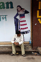 A man sits next to an advertisement in a market in central Kolkata.<br />