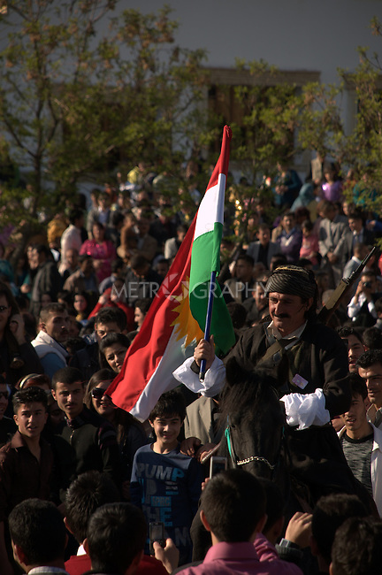 SULAIMANIYAH, IRAQ: A horseman rides through the crowd holding a Kurdish flag...Newroz, celebrated across the world on the vernal equinox, is the official beginning of the Kurdish calendar and the first day of spring.  Kurds celebrate Newroz on March 20th and 21st by lighting fires and performing traditional dances...Photo by Pazhar Muhamad/Metrography