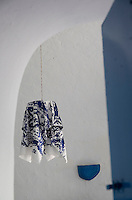 Glimpsed through an open door a pendant light draped in a blue and white cotton hangs against a whitewashed wall